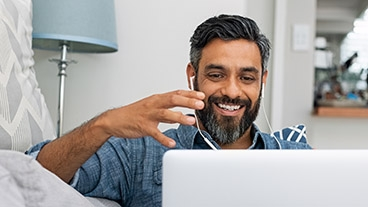 man with beard using a virtual consultation with headphones and laptop