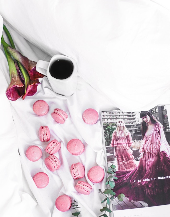 pink macaroons, coffee, pink flowers, and a fashion magazine on a white bed for valentines day decor