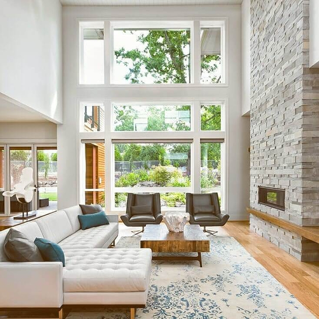 pella triple pane windows floor to ceiling windows white and cream vintage rug gray stone fireplace