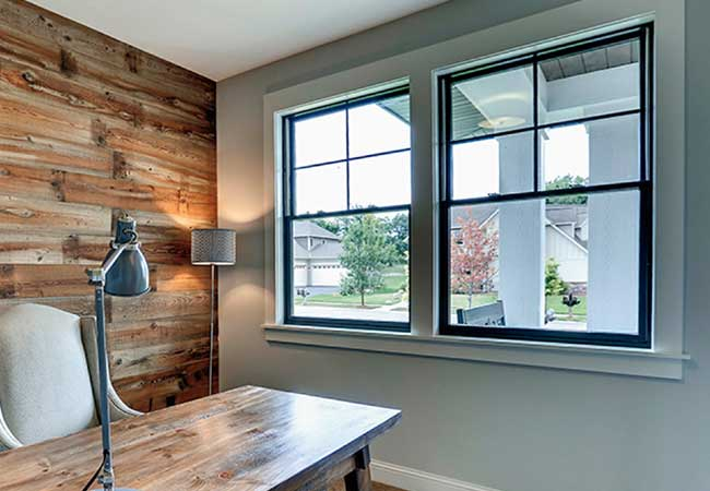 A home office with a rustic desk and wall with two black-trimmed windows on a white wall