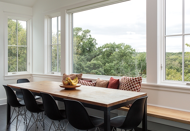 A large contemporary dining room table with a wall of windows bringing in much light