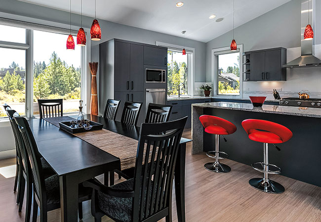 Red lights over a contemporary black table in a modern kitchen
