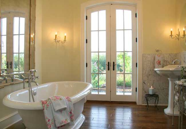Free-standing bathtub with a wildlife view through hinged patio doors