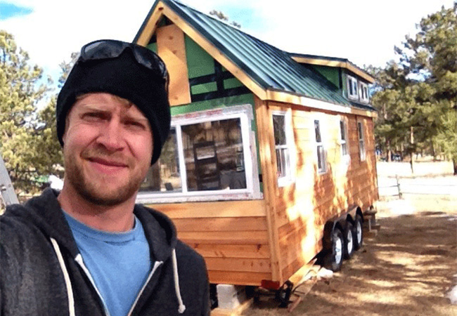 Jonathon takes a selfie after finishing up building a tiny home