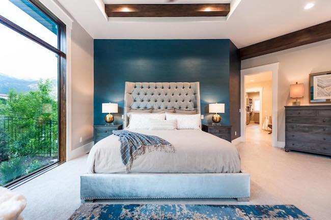 large master bedroom with deep jewel-toned walls, a fabric headboard on a king-size bed, and large architect series wood windows