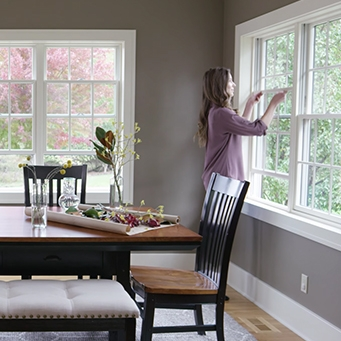 woman opening a lifestyle series double-hung window