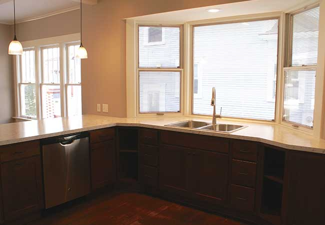 A bay window behind the sink in an open concept kitchen