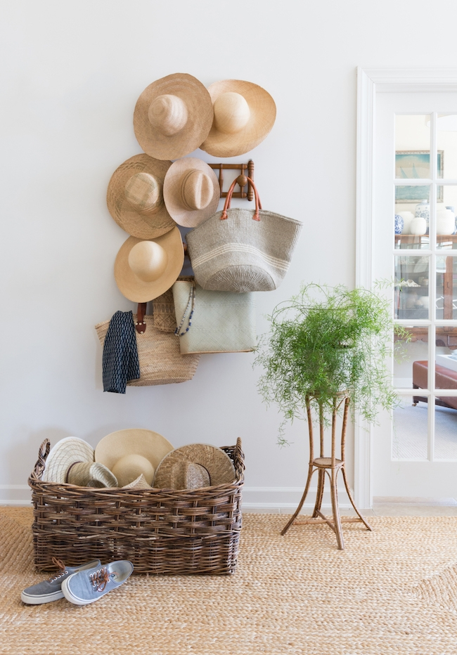 matthew caughy interiors entryway with lots of straw hats, both hanging on the wall and in a wicker basket on the floor.