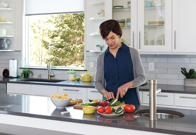 Woman prepares food in a whilte and gray kitchen flooded with natural light from the window over the sink