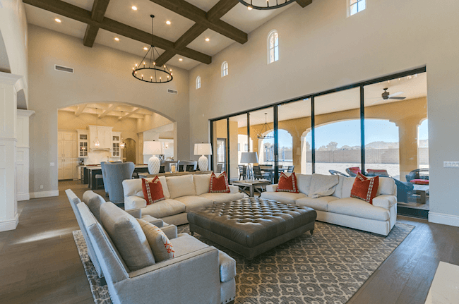 exposed wood ceiling beams and tufted ottoman chandelier expansive scenescape doors