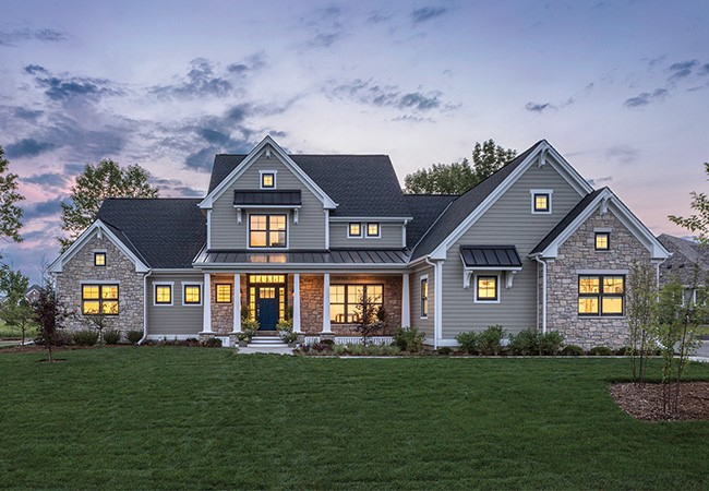 A large newly-built home at dusk with interior lights on
