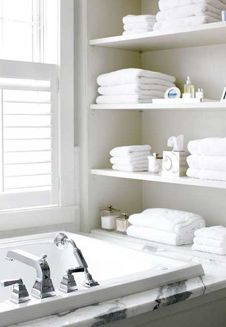 Open shelving unit for towels next to the bathtub