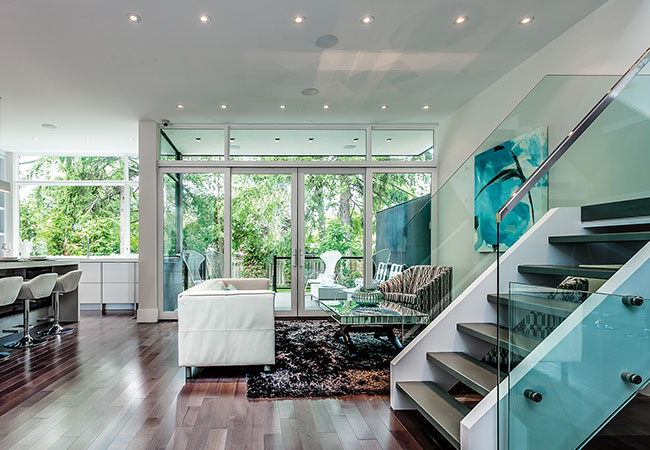 Recessed lighting over an open-concept living room and kitchen with teal accents