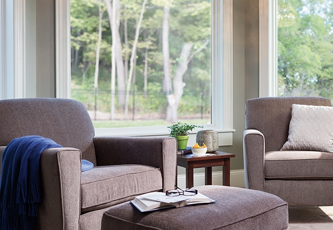 Natural chairs and ottoman sitting in front of a large, white casement window looking out to a backyard with trees