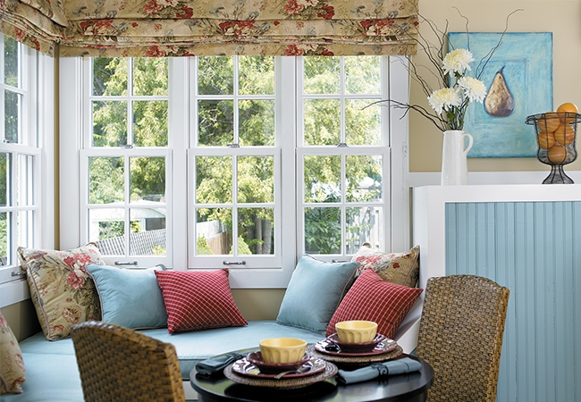 a corner of windows with white trim and blue decor