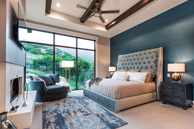 Master bedroom with dark jewel toned walls, a large king-size bed, fireplace, and large architect series windows looking out over hills.