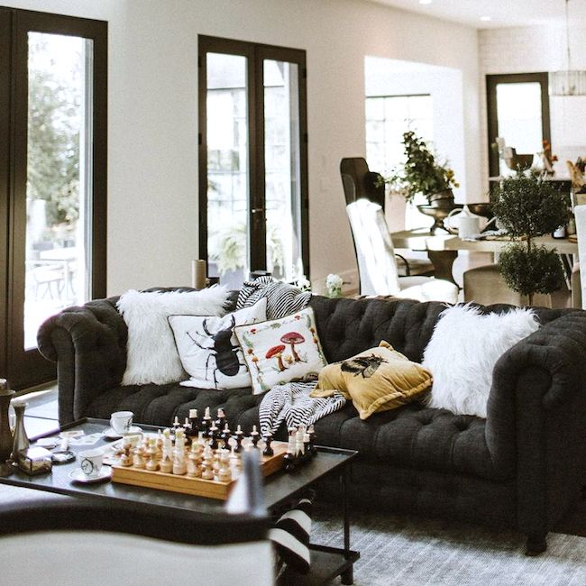 lexi in the hutch living room with a large black couch and white throw pillows, a black coffee table with a classic chess board and black-trimmed windows and patio doors.
