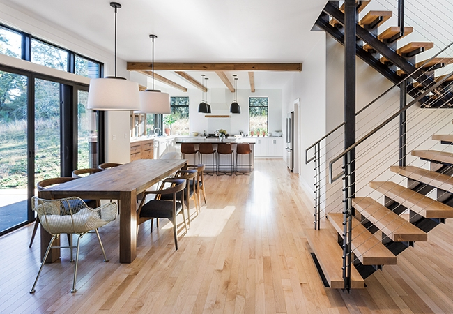 wood midcentury dining table in open living space with wall of windows and modern staircase