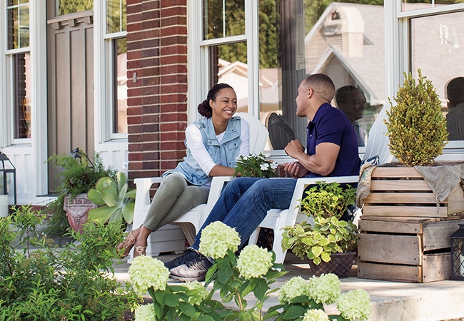 A couple sits on the patio outside of their brick home