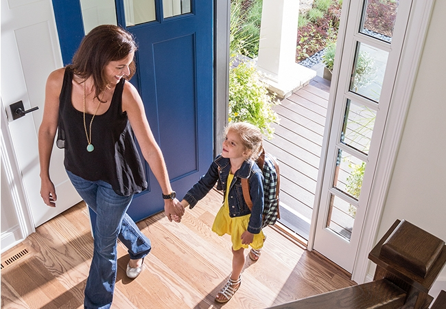 Interior view of a mom and daughter returning home by a blue entry door