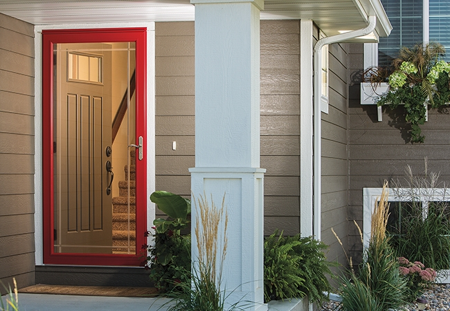 Exterior view of a home with a red screen door