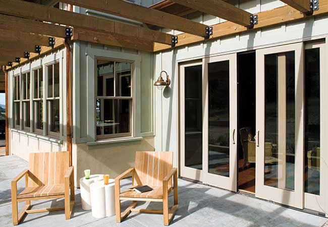 Rustic patio with wooded patio furniture and French sliding patio doors