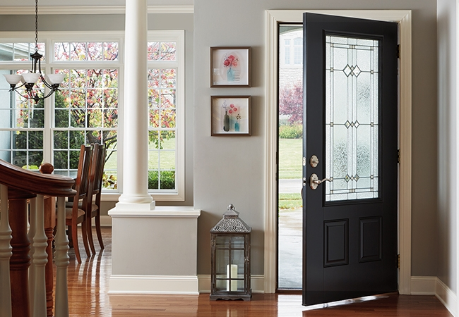 A black entry door is half opened to a clean living room