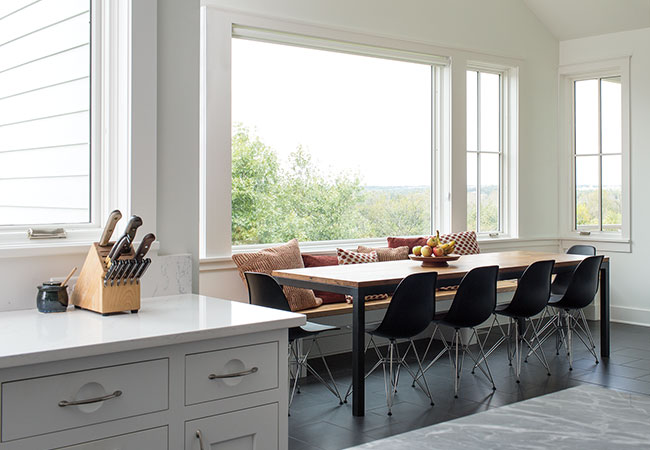 A minimalist kitchen with large fixed windows bringing in natural light