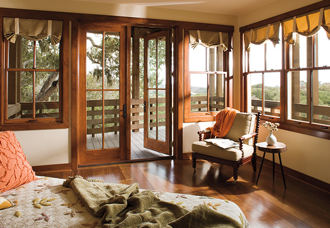 A bedroom with hardwood floors and wood trimmed windows and a hinged patio door leading out to a deck