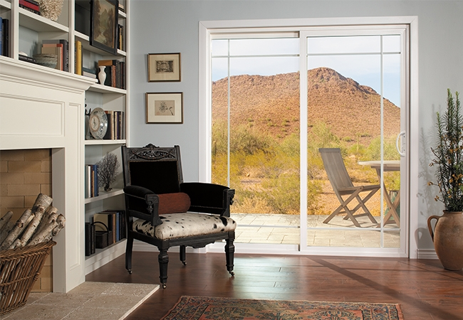 Interior view of a living room chair next to a sliding patio door and fireplace