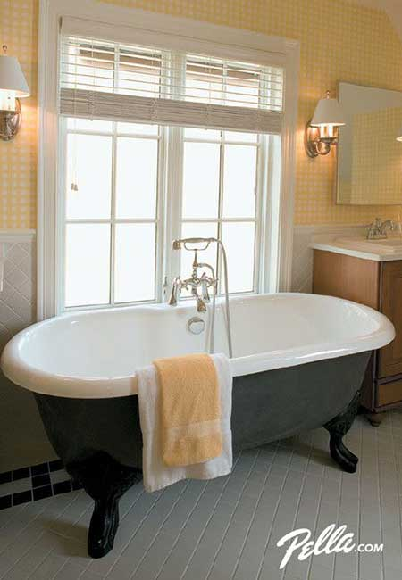 Clawfoot free-standing bathtub next to a large casement window letting in natural light