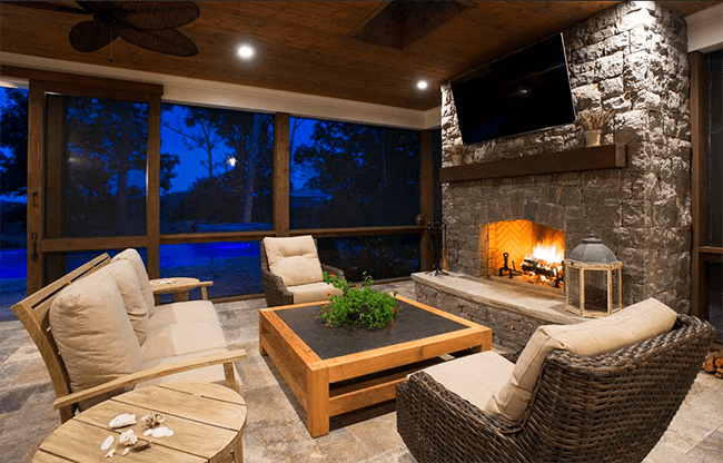 fireplace design ideas gray stone fireplace brown patio chairs nighttime natural wood ceiling