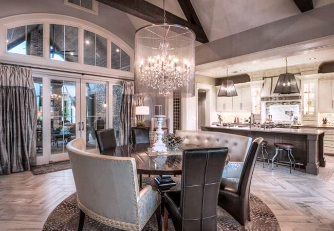 A showstopping spacious kitchen with metallic coloring and cushioned dining room chairs.