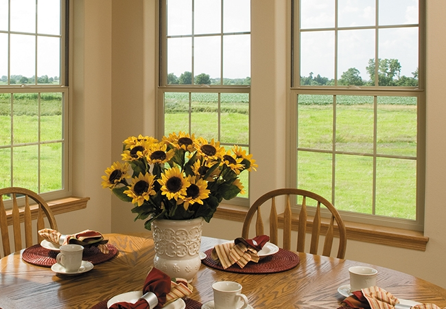 a dining room table with sunflowers surrounded by natural light