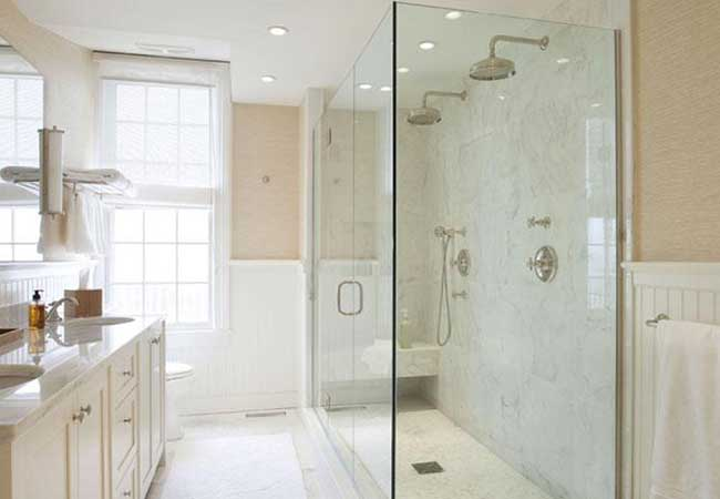 Clear walls surround a large shower with two shower heads