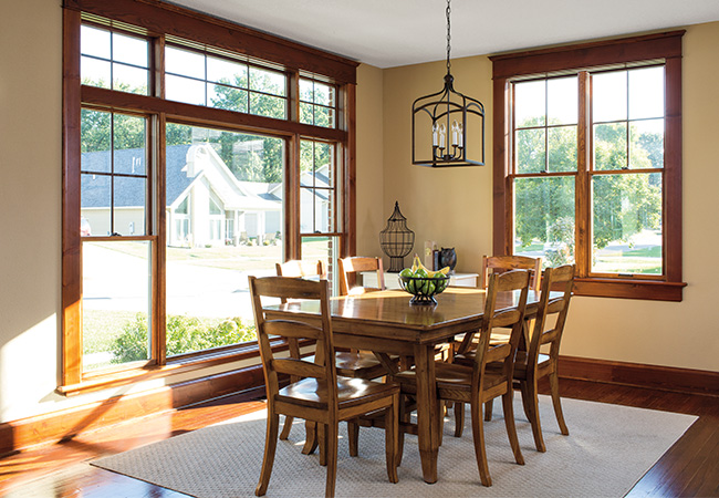 Dining room with plenty of sunlight from wood-trimmed windows and a classic wooden dining room set.