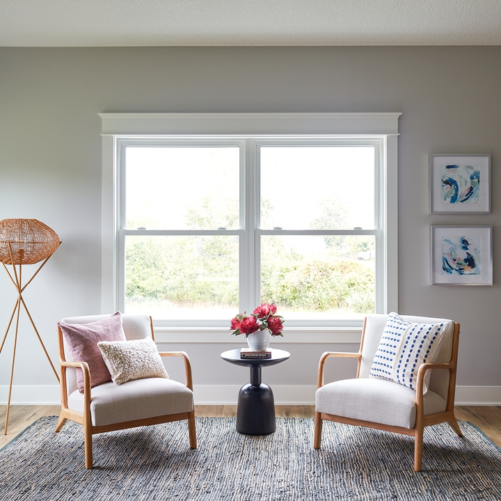 living room with two wood chairs and two double-hung windows behind