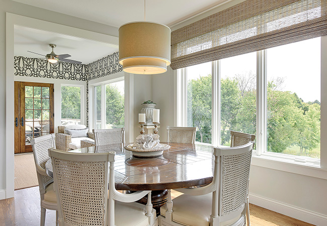 Cream colored dining room surrounded by windows looking out to a grove of trees.