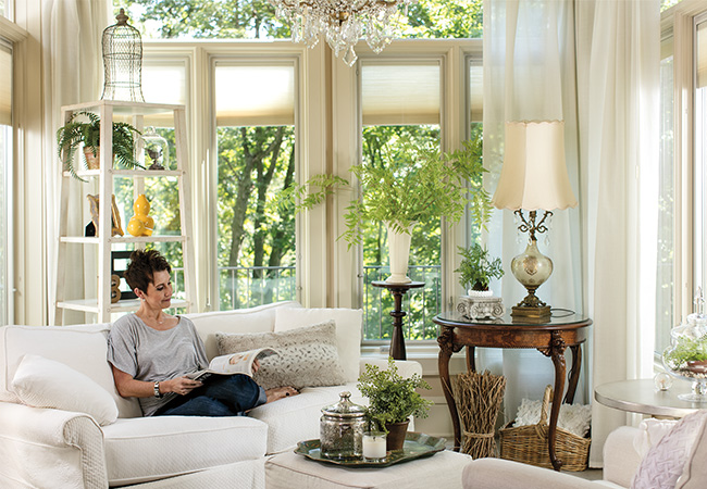 A woman relaxes on her white sofa and reads a magazine in a living room surrounded by greenery.