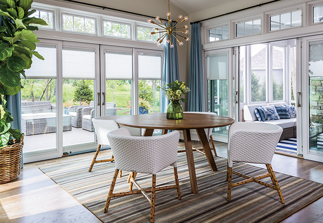Contemporary dining room surrounded by Designer Series Hinged Patio doors which open to a patio and a porch.
