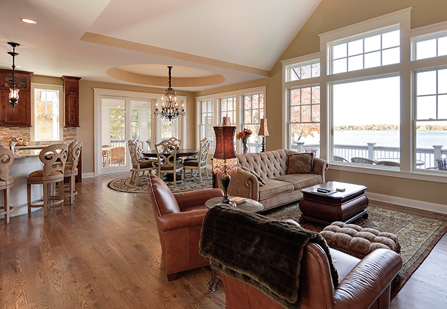 A warmly decorated living room with hardwood floors and rich brown leather furniture and warm tan walls.