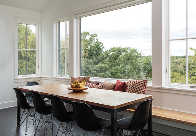 Bright dining room with plenty of white-trimmed fixed and casement windows and a contemporary dining room table.