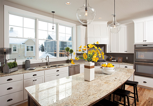 A bright white kitchen lets in a lot of sunlight with 3 windows and a marble countertop with yellow flowers in a vase on the island.