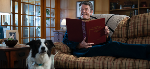 John Michael Higgins sitting on the couch with his dog