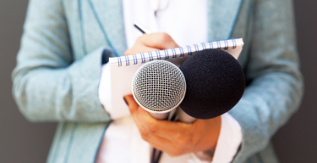 Reporter holding microphones