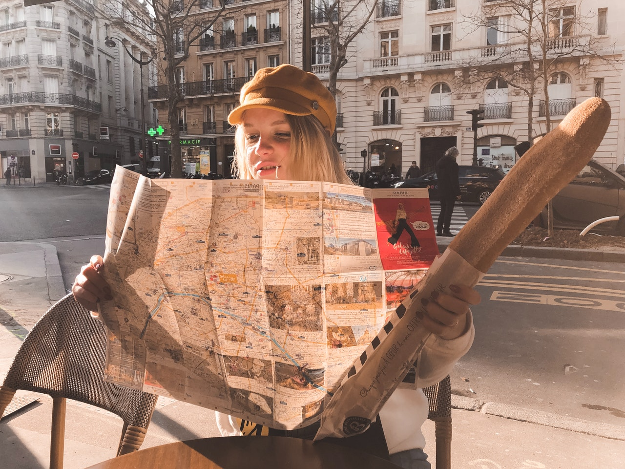 Woman with baguette reading a map itinerary of Romance languages list of countries