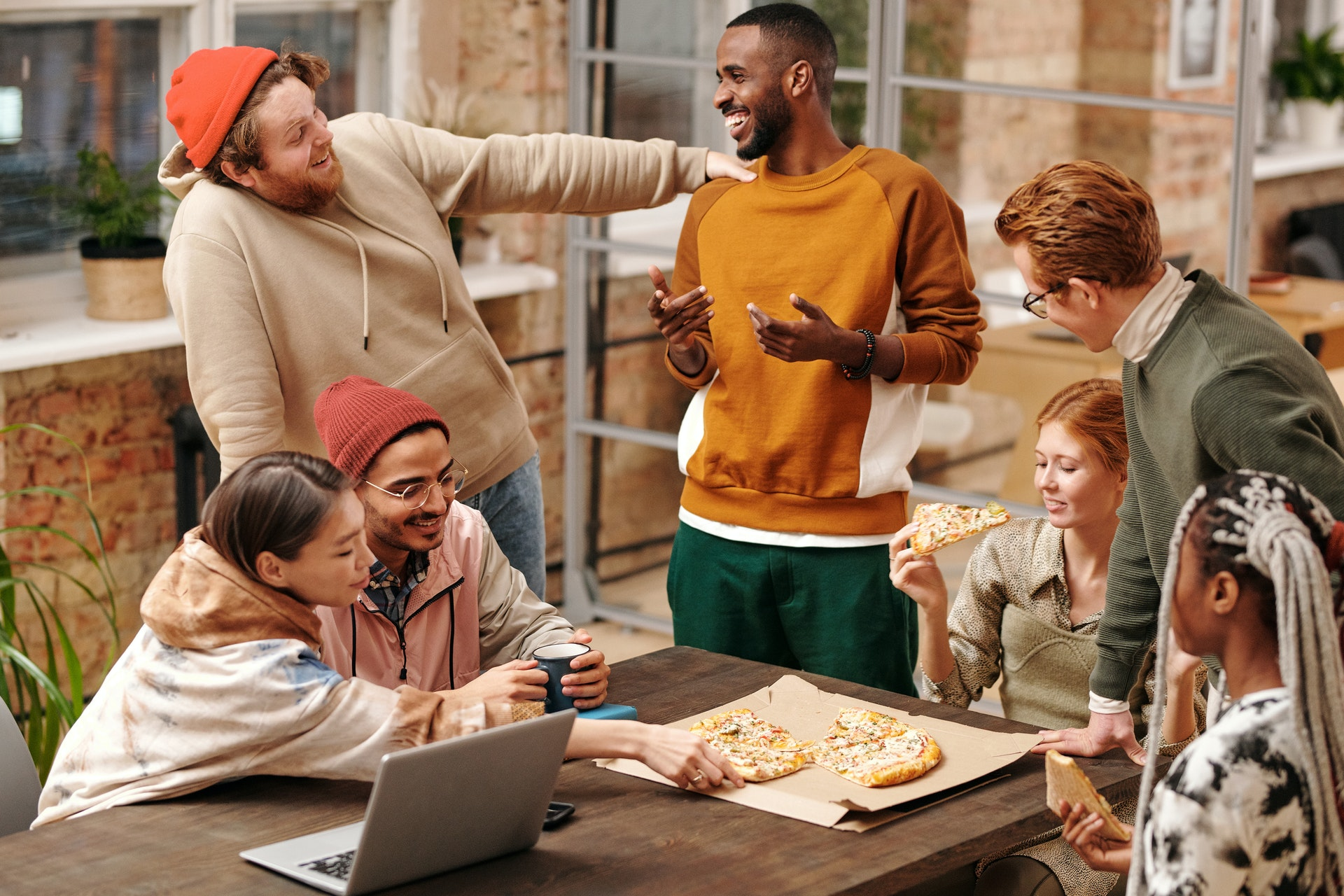 Cultural competence in the workplace example of diverse colleagues sharing pizza o
