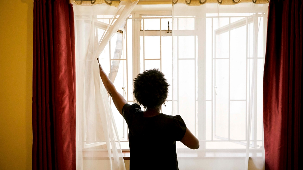 A woman stands facing an open window with sheer white curtains.