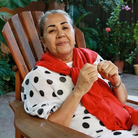 Žena v bodkovaných šatách a červenou šatkou sedí na drevenej stoličke.