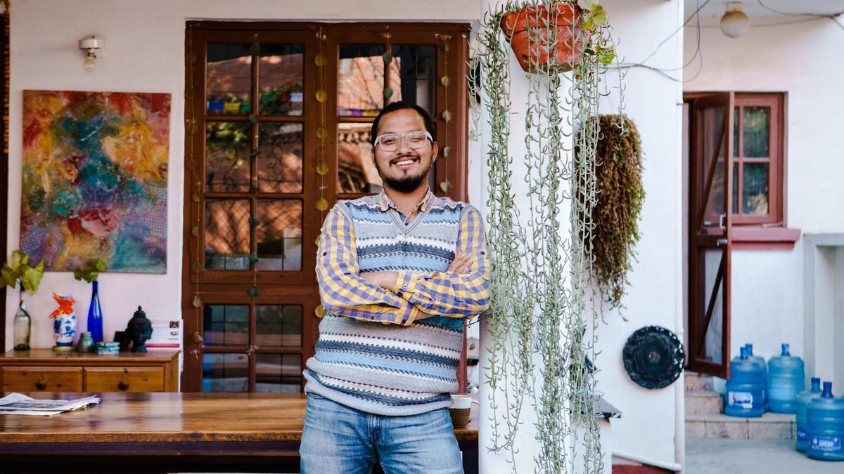 Ein Mann mit Brille und einer gestreiften Weste lehnt an der Außenseite eines Gebäudes mit Hängepflanzen und Kunstwerken an den Wänden.